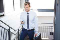 Businessman using phone and climbing staircase Stock Photography