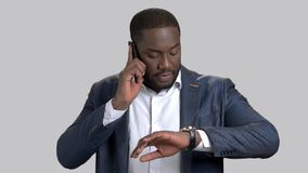 Businessman using phone and looking on wristwatch. Confident afro-american businessman talking on mobile phone and checking his wristwatch on grey background stock video footage
