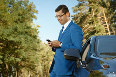 Businessman using phone nearby his car. Handsome businessman using phone while leaning on car Stock Images