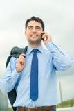 Businessman using phone on travel Stock Image