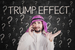 Businessman using a phone with Trump Effect word Stock Photos