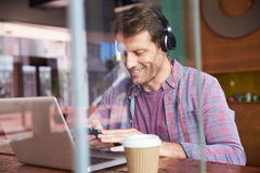 Businessman Using Phone Working On Laptop In Coffee Shop Stock Photo