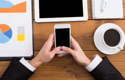 Businessman using phone at workplace, top view, close up Stock Photos