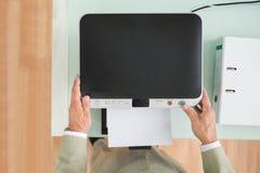 Businessman using photocopy machine. High Angle View Of A Businessman Using Photocopy Machine In Office Royalty Free Stock Photo