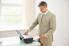 Businessman using photocopy machine Stock Photo