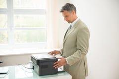 Businessman using photocopy machine. Mid-adult Businessman Using Photocopy Machine In Office Royalty Free Stock Photos