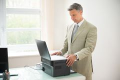 Businessman using photocopy machine. Mid-adult Businessman Using Photocopy Machine In Office Stock Photo