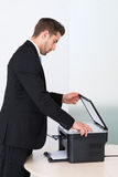 Businessman Using Photocopy Machine In Office. Side view of young businessman using photocopy machine in office Royalty Free Stock Photos