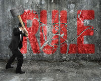 Businessman using sledgehammer cracking red rule word broken Stock Photography