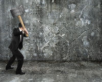 Businessman using sledgehammer cracking wall broken on concrete Stock Photography