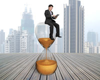 Businessman using smart pad sitting on hour glass. With city skyscrapers and wooden floor royalty free stock photo