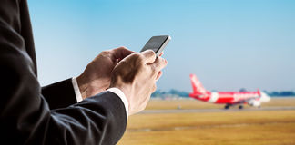 Businessman using smart phone with airplane background, concept of online checking in, mobile on plane and etc. Stock Images