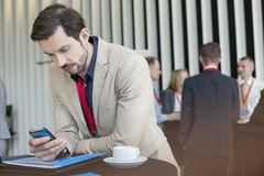 Businessman using smart phone while coffee break in convention center.  Royalty Free Stock Photo
