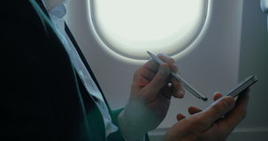 Businessman using smart phone during the flight. Close-up shot of a businessman using pen to type on smartphone in the plane. Communication during the flight stock video