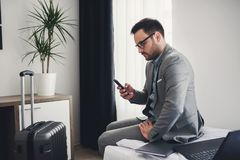 Businessman using smart phone at hotel room royalty free stock image