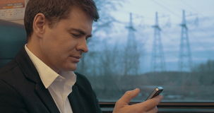 Businessman using smart phone during trip in train stock footage