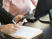 Businessman Using Smart Phone While Writing On Document At Desk. Midsection of businessman using smart phone while writing on document with colleague at desk in Stock Image