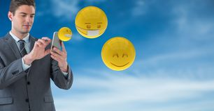 Businessman using smart phones while emojis flying against sky. Digital composite of Businessman using smart phones while emojis flying against sky Royalty Free Stock Photo
