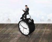 Businessman using smart tablet sitting on alarm clock Stock Photo