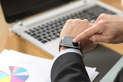 Businessman using a smart watch at office Stock Image