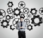 Businessman using smartphone against. A white wall drawn with engine gear wheels royalty free stock photos