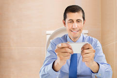 Businessman using smartphone at the bathroom Stock Image