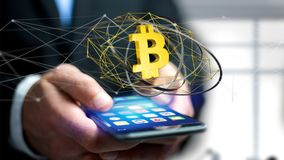 Businessman using a smartphone with a Bitcoin crypto currency si. View of a Businessman using a smartphone with a Bitcoin crypto currency sign flying around a Stock Photography