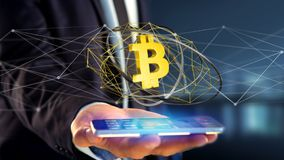 Businessman using a smartphone with a Bitcoin crypto currency si. View of a Businessman using a smartphone with a Bitcoin crypto currency sign flying around a Stock Image