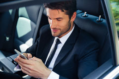 Businessman using smartphone in car Royalty Free Stock Photo