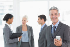 Businessman using a smartphone with colleagues behind in office Royalty Free Stock Photos