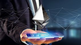 Businessman using a smartphone with a Ethereum crypto currency s. View of a Businessman using a smartphone with a Ethereum crypto currency sign flying around a Stock Photography