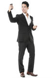 Businessman using a smartphone. Exhilarated businessman using a smartphone Royalty Free Stock Photos