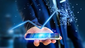 Businessman using a smartphone with a  Financial arrow going up. View of a Businessman using a smartphone with a  Financial arrow going up and explosing at the Stock Photos