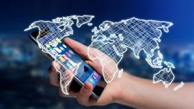 Businessman using a smartphone with a Hand drawn world map on a. View of a Businessman using a smartphone with a Hand drawn world map on a futuristic interface Stock Photo