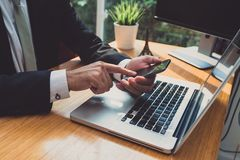 Businessman using smartphone and laptop computer Royalty Free Stock Photos