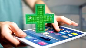 Businessman using a smartphone with a Lighting pharmacy cross an. View of a Businessman using a smartphone with a Lighting pharmacy cross and a stethoscope - 3d Royalty Free Stock Image
