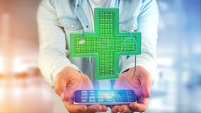 Businessman using a smartphone with a Lighting pharmacy cross an. View of a Businessman using a smartphone with a Lighting pharmacy cross and a stethoscope - 3d Royalty Free Stock Photography