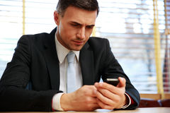 Businessman using smartphone at office. Confident businessman using smartphone at office Royalty Free Stock Photo