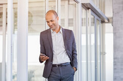Businessman using smartphone at office. Happy mature businessman in formal using smartphone in modern office. Successful senior business man smiling on reading Stock Photos