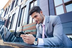 Businessman using smartphone outdoors Royalty Free Stock Images