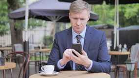 Businessman Using Smartphone while Sitting in Outdoor Cafe. The Businessman Using Smartphone while Sitting in Outdoor Cafe, high quality stock video footage
