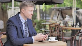 Businessman Using Smartphone Sitting in Outdoor Cafe. The Businessman Using Smartphone Sitting in Outdoor Cafe, high quality stock video footage