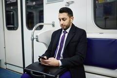 Businessman Using Smartphone on Subway train royalty free stock image