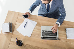 Businessman using smartphone while working on laptop at workplace Royalty Free Stock Photo