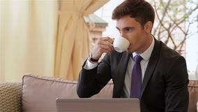 Businessman using a smartphone. Young businessman using a laptop and a smartphone for a coffee break. Businesspeople having business lunch outside on the terrace stock footage