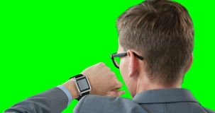 Businessman using smartwatch. Against green background stock footage