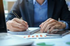 Businessman using smatphone for analysis maketing plan stock image