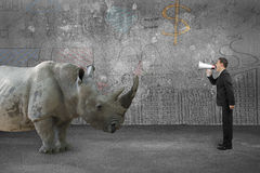 Businessman using speaker against rhinoceros with doodles wall Stock Photo