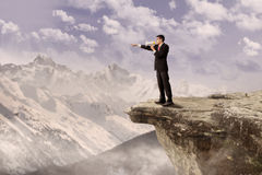 Businessman using speaker on cliff. Young businessman using speaker on top of a high mountain Royalty Free Stock Photo