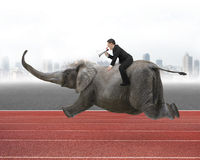 Businessman with using speaker riding on elephant. With city skyline and red track background Royalty Free Stock Photos